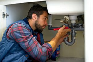 man-fixing-pipes-under-the-sink